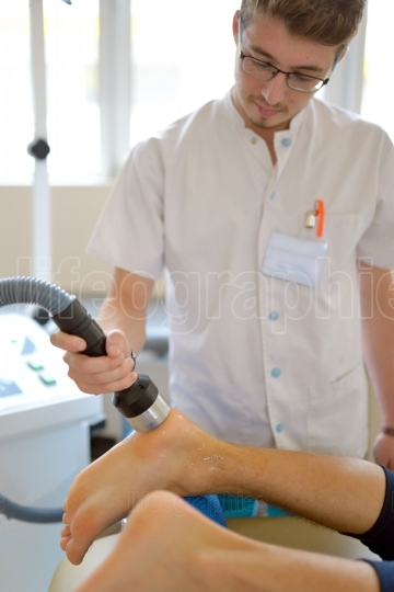 Physiotherapist performs ultrasound therapy treatment