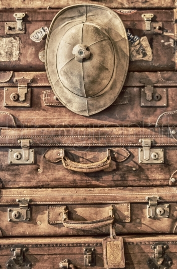 Pile of antique luggage suitcases with Salacot hat