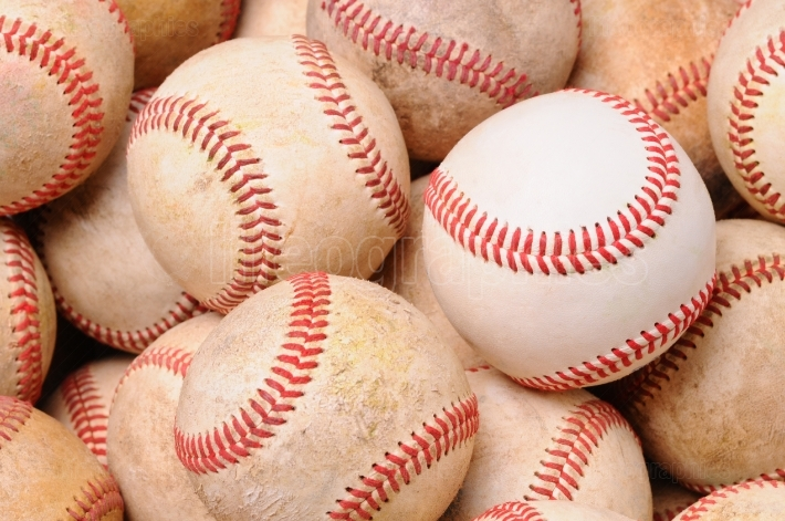 Pile of Old Baseballs with one new ball
