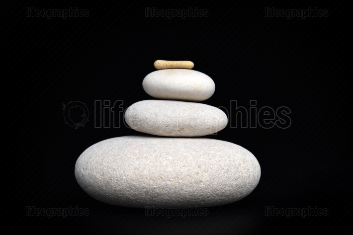 Pile of white sand stones against black background
