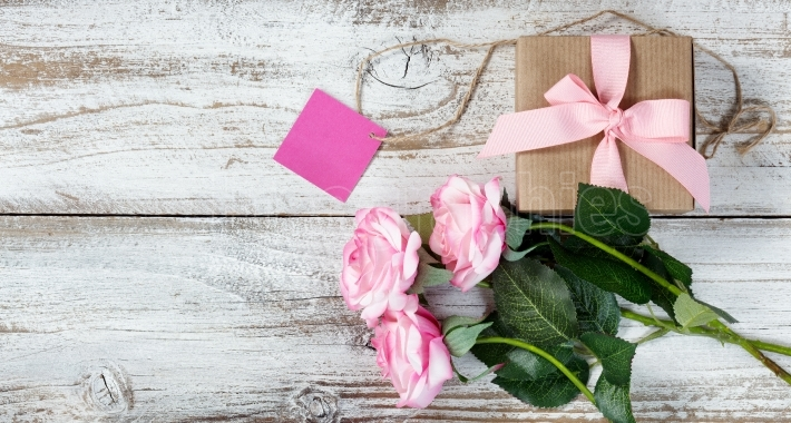 Pink roses and gift on rustic white wood