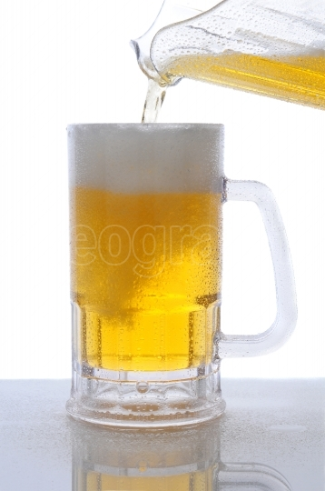 Pitcher of Beer Pouring into Mug