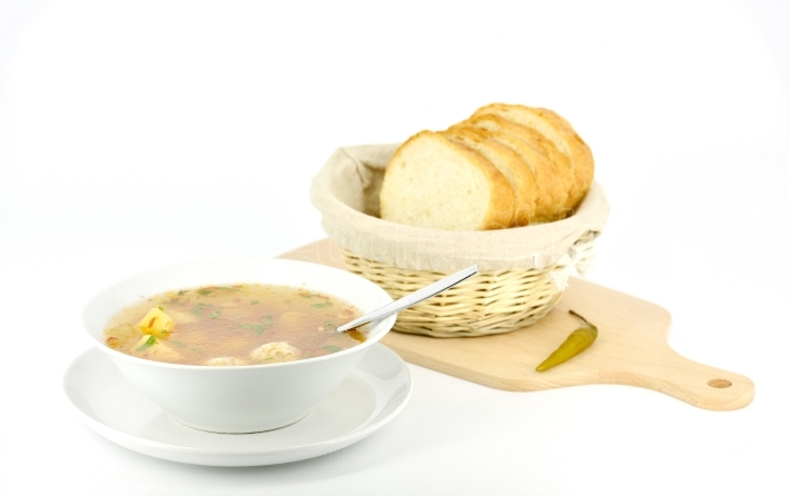 Plate with soup and bread against white background