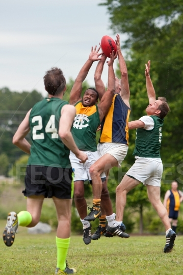 Players battle for ball in australian rules football game