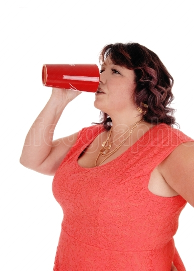 Plus sized woman drinking from red mug