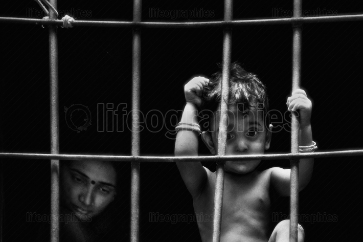 Poor child and his mother watch outside the house through the bars of the window