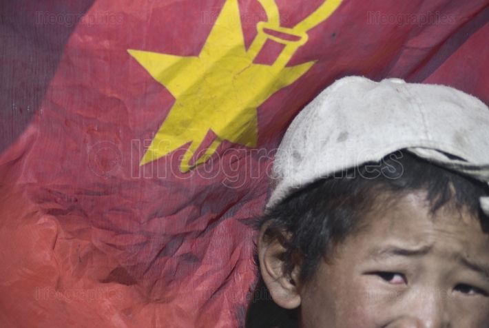 Poor kid from Tibet holding the Chinese flag