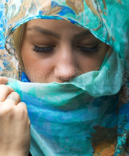 Portait of woman wearing a blue scarf with eyes closed
