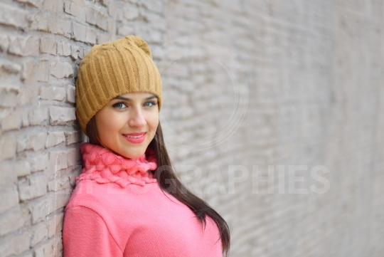 Portrait fashion cool girl in colorful clothes over wooden background wearing a  hat and pink  sweater