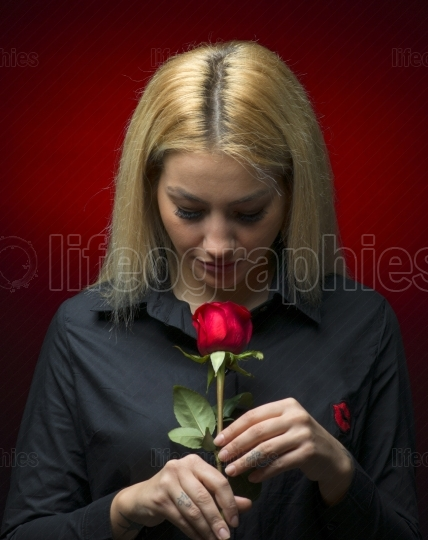 Portrait of a beautiful blonde girl smelling a red rose isolated