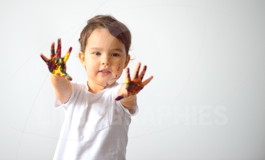 Portrait of a cute little girl showing her hands painted in bright colors