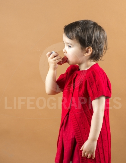 Portrait of a girl using asthma inhaler