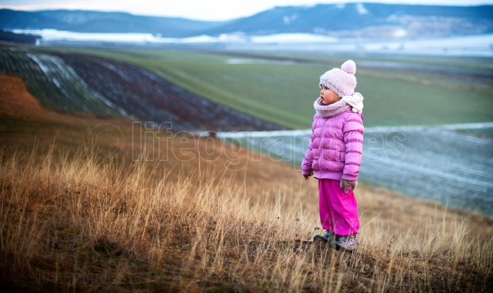 Portrait of a little girl alone in the field. Winter time