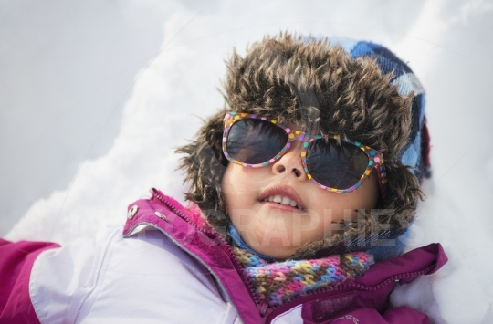 Portrait of a little girl in the snow with winter clothes and sunglasses