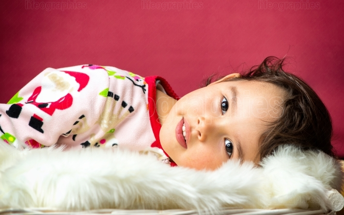 Portrait of little cute girl in bed isolated on red