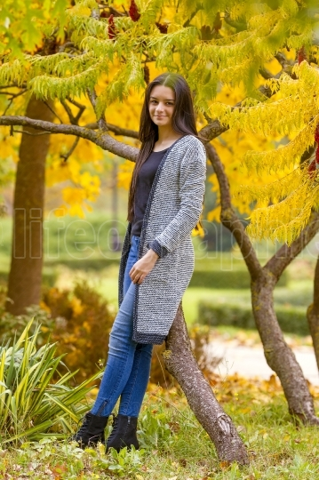 Portrait of pretty teen girl in autumn park