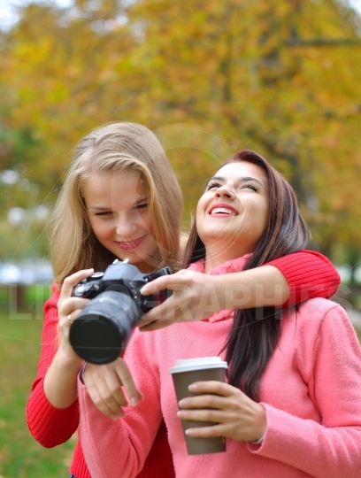 Portrait of two happy female, Caucasian friends taking photos with a DSLR camera.