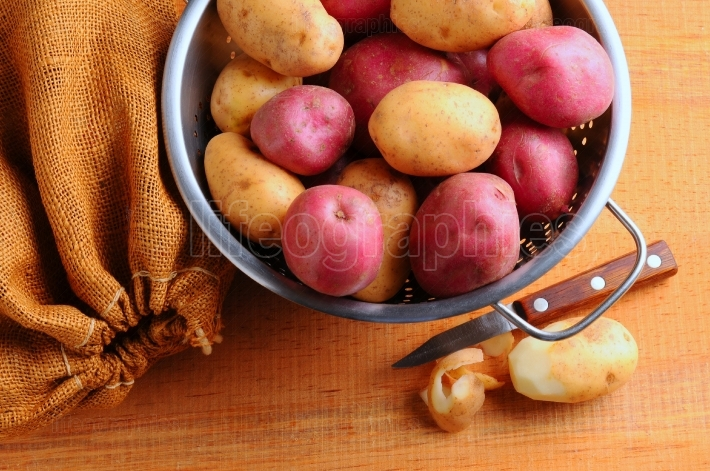 Potatoes in Colander with Burlap Sack and Paring Knife