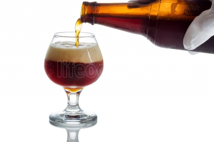 Pouring fresh cold beer into glass goblet