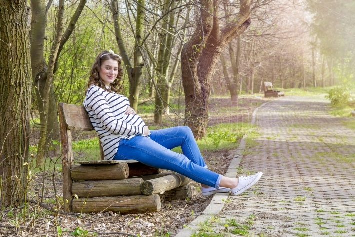 Pregnant woman outdoor in the park on bench