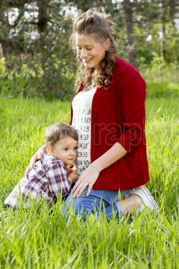 Pregnant woman outdoor with her little boy