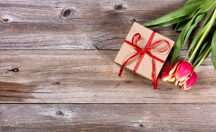 Present and flowers on stressed wood background