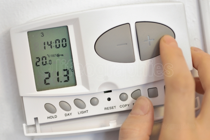 Pressing button on digital thermostat