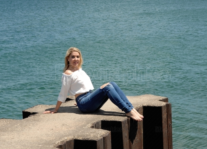 Pretty girl sitting on pier on lake.