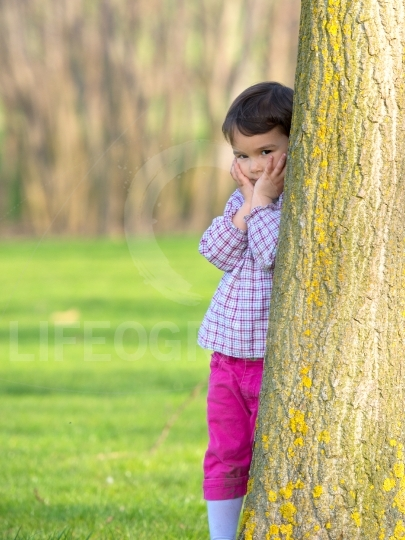 Pretty little girl peeking out from behind a tree