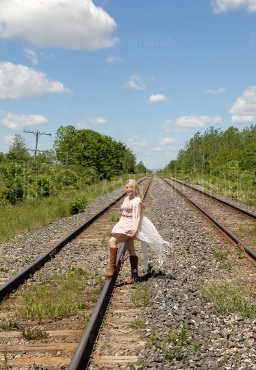 Pretty woman walking on railroad truck's.