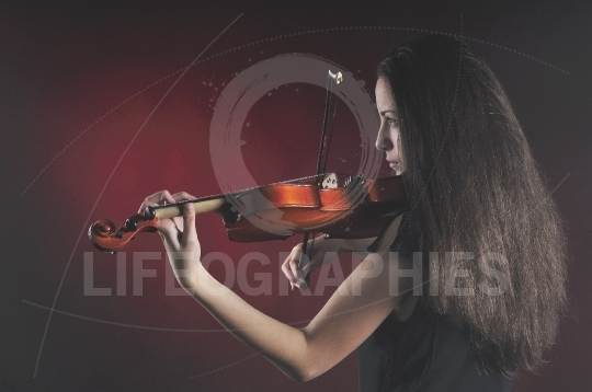 Pretty young woman with long beautiful hair playing a violin