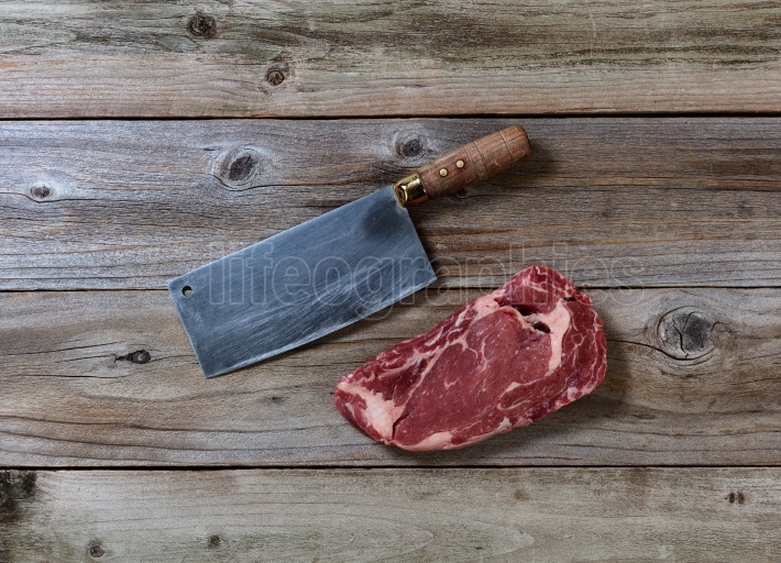 Prime Beef Steak with Butcher Knife on rustic wood