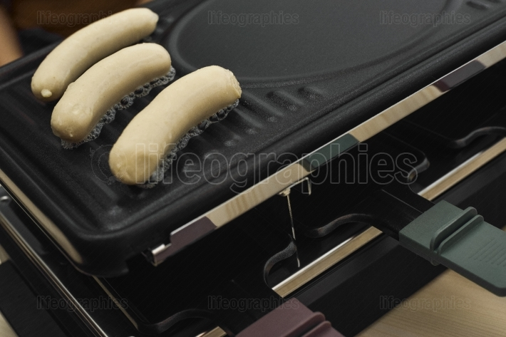 Raclette table-top with sausages