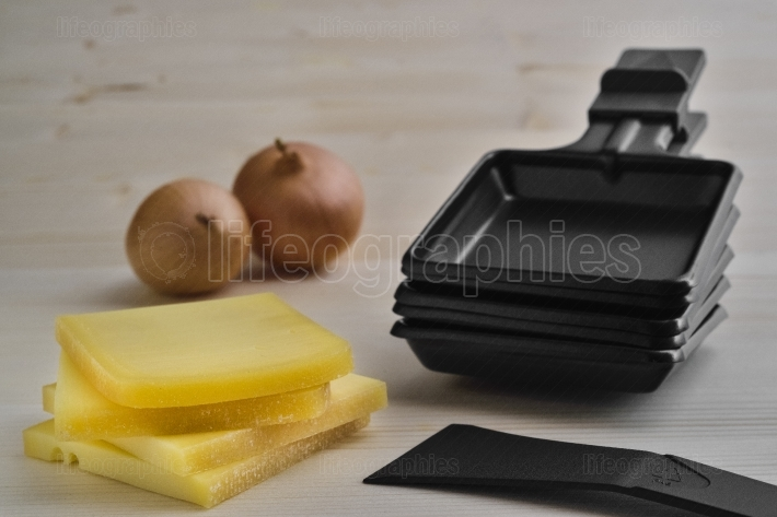 Raclette trays with cheese, potatoes and onion