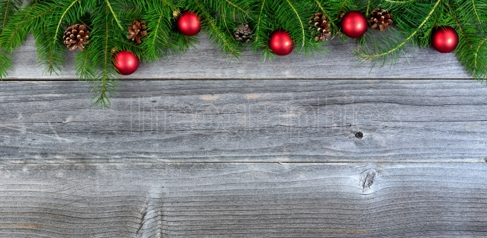 Real Christmas fir tree branches and Red ornaments on weathered