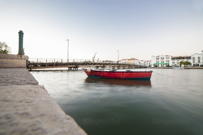 Red fishing boat at the mooring near Tavira down town, Portugal