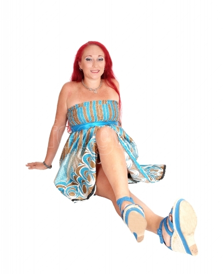 Red hair woman sitting on floor.