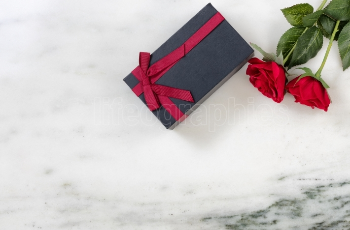 Red Roses and packaged gift box on marble stone background