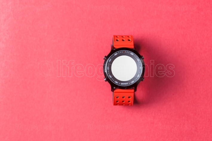 Red smartwatch on red background