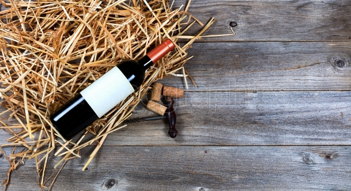 Red wine bottle with vintage wine corkscrew on straw and rustic