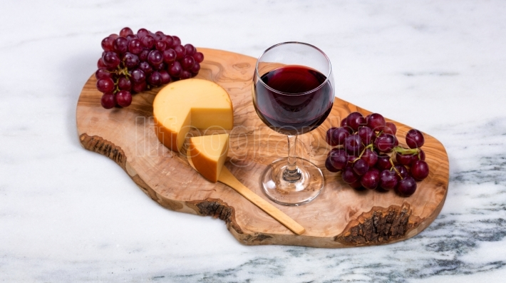 Red wine with gourmet cheese and grapes on wooden server