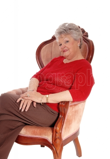 Relaxed senior woman sitting in armchair.