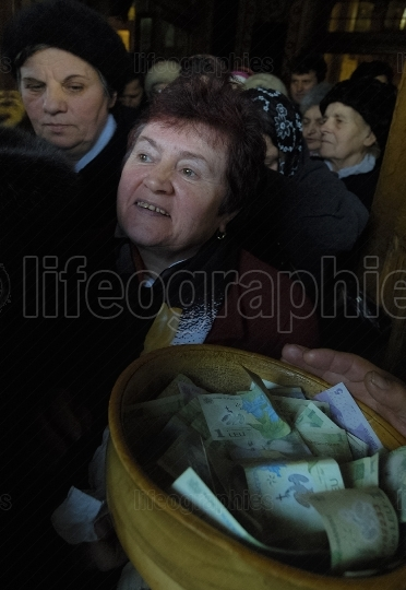 Religious people inside Sighisoara church  donate non-taxed money.