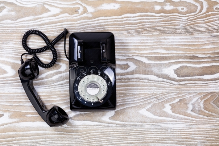 Retro telephone on faded wooden surface