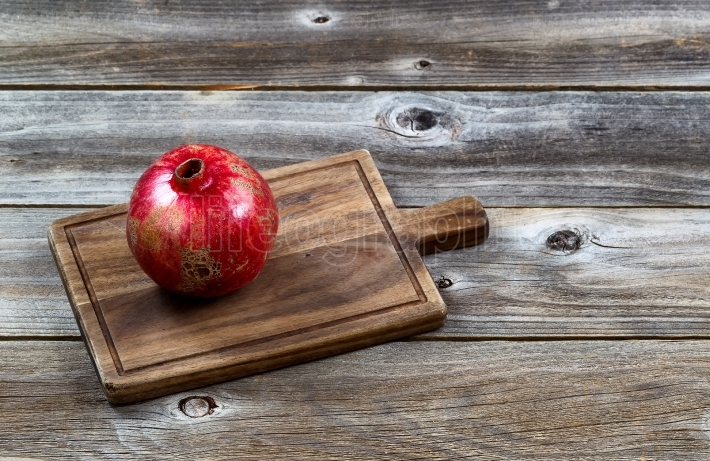 Ripe Whole Pomegranate on Vintage Wooden server board