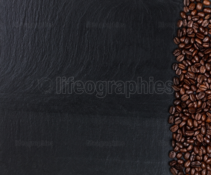 Roasted coffee beans on natural dark slate stone