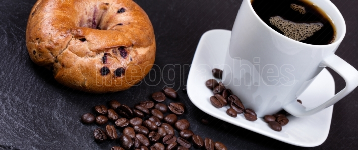 Roasted coffee beans with drink and bagel in background on slate
