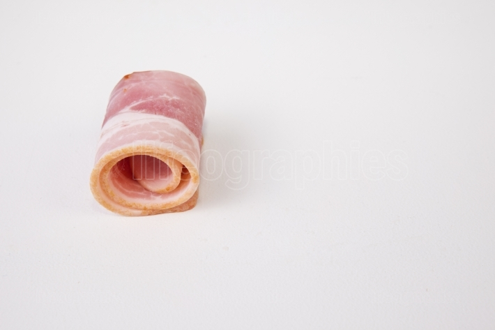 Rolled raw bacon slice