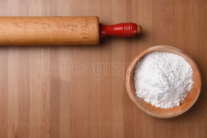 Rolling pin and bowl of flour on a wood background