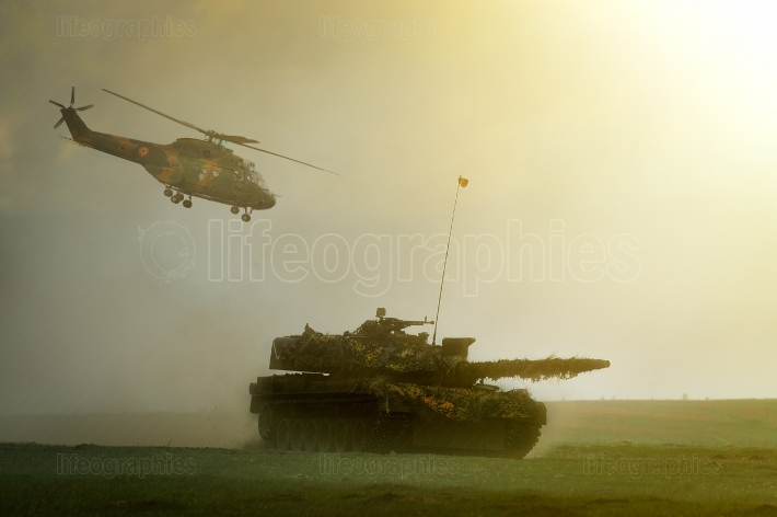 Romanian tank TR-85M1 and military helicoter IAR 330 Puma in military polygon